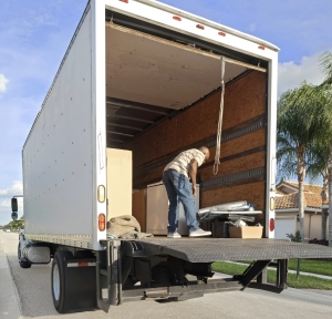 Delivery driver unloading a straight truck using liftgate